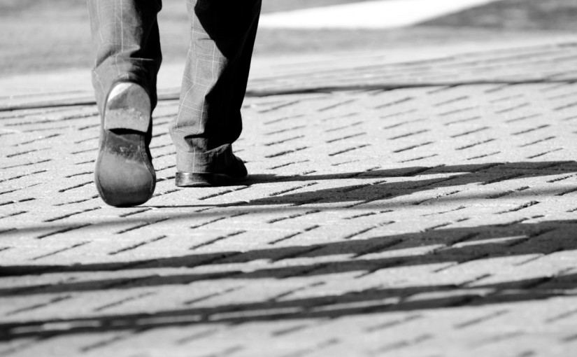 Close up from behind: shoes walking forward (B&W).