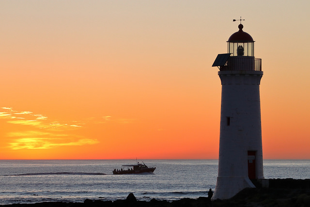 Lighthouse and boat with sunset in the background.
