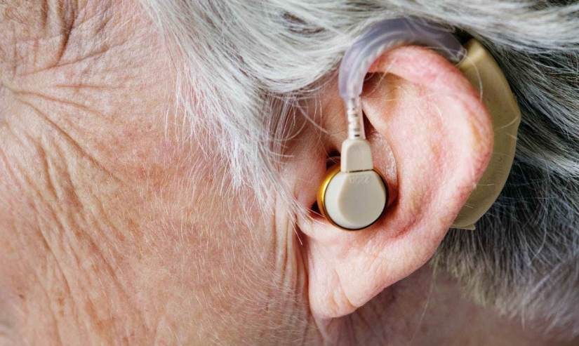 Close-up of hearing aid in elderly person's ear.