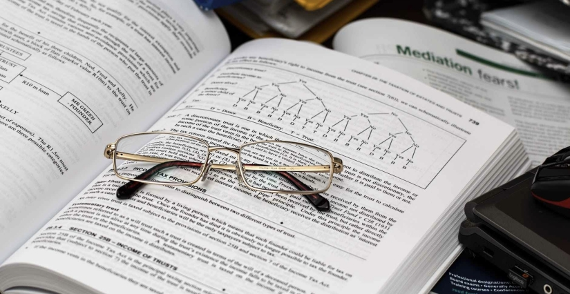 Folded glasses set atop an open accounting book.