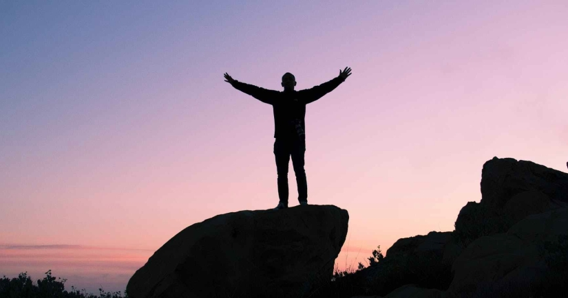 Silhouette with arms raised on top on a mountain.