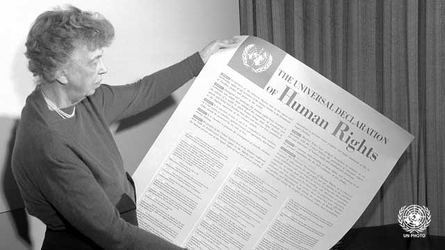B&W; Woman holds up a huge piece of paper entitled The Universal Declaration of Human Rights.