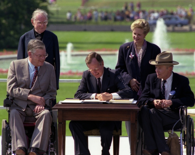 2 people in wheelcharis & 2 standing people look on as a man signs a document.